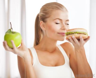 woman-smelling-hamburger-while-holding-apple